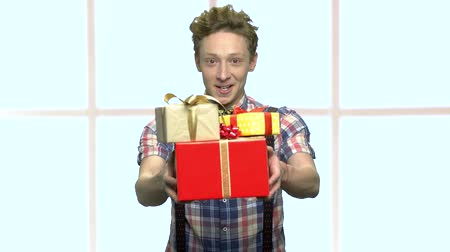 bonus : Teen boy holding stack of gifts. Shy teenage boy giving gift boxes on checkered window background. Holiday greeting concept.