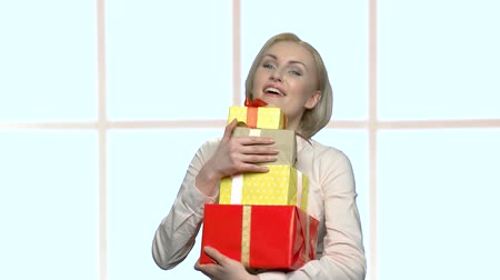 bonus : Portrait of happy woman with a pile of gifts. Attractive business woman holding a lot of presents, front view. Gifts for Womens Day. Stock Footage