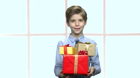 bonus : Portrait of boy with gift boxes. Cheerful kid holding many gift boxes on abstract window background. Holiday sales concept. Stock Footage