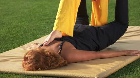 masażysta : Woman is getting shiatsu massage outdoors. Feet massaging womans back. Thai yoga therapy. Pain relief concept.