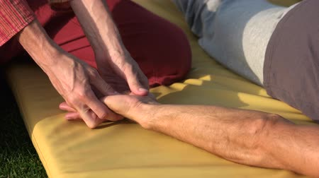 akupresura : Relaxed man receiving hand massage outdoors. Male physiotherapist giving hand massage to male client. Effect of acupressure therapy.