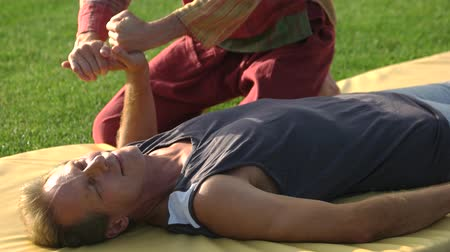 masażysta : Caucasian man receiving Thai hand massage. Relaxed man lying on mat and getting palm massage. Professional acupressure manipulations.