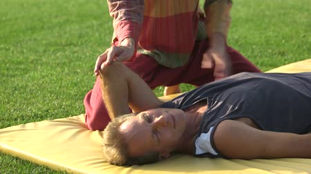 łokieć : Elbow stretching on mat, Thai massage. Lying relaxed man receiving massage outdoor in the park. Body massage therapy. People and healthy lifestyle.