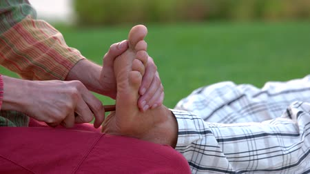 akupresura : Thai foot massage treatment. Close up masseur giving relaxing reflexology Thai foot massage with wooden stick to man outdoors. Wideo