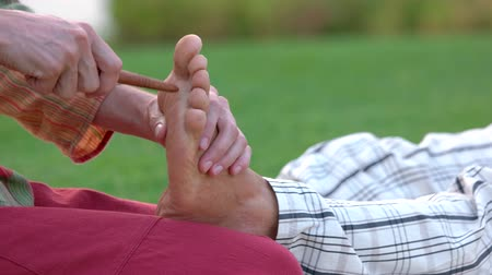 blood circulation : Reflexology foot massage to man. Thai spa foot treatment by wood stick outdoors. Healing benefits of foot reflexology massage.