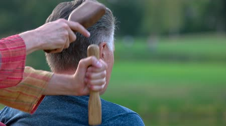 ayurveda : Tapping hammer masssage outdoors. Thai massage with tapping body with wooden hammer. Hammer therapy for back pain.