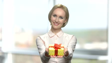 főnyeremény : Beautiful lady giving gift box. Pretty woman presents small yellow present box on blurred background. Seasonal sale concept. Stock mozgókép