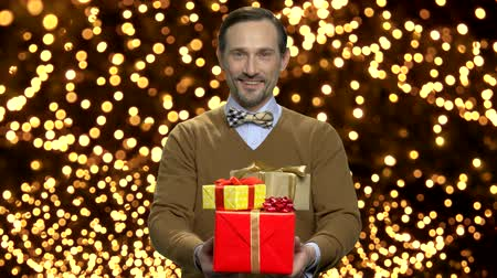 golden ribbon : Man giving gift boxes on New Year background. Handsome bearded man handing gift boxes on abstract background of blurry golden lights. Stock Footage
