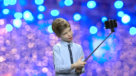 newyear : Funny child holding selfie stick. Cute litttle boy making grimace while taking selfie with monopod. Kids and modern technology. Blue bokeh lights background. Stock Footage