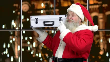 santaclaus : Santa with metal case of money. Businessman in costume of Santa Claus is opening silver case on evening city background. Financial and business theme.