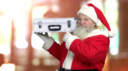 dava : Smiling Santa holding silver case. Authentic Santa Claus on blurred background. Magic Christmas atmosphere.