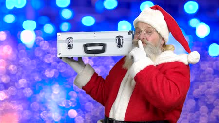 santaclaus : Santa with silver case on blue bokeh background. Traditional Santa Claus showing silence gesture. When dreams come true. Stock Footage