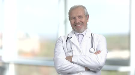 stojan : Cheerful senior doctor, blurred background. Caucasian elderly doctor standing arms crossed and carrying stethoscope on shoulders at hospital. Dostupné videozáznamy