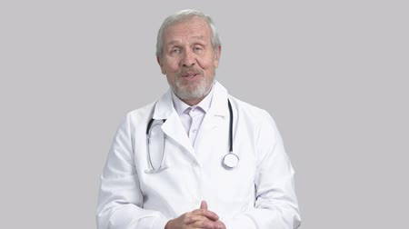 do widzenia : Doctor talking to camera, gray background. Senior male doctor with medical equipment, portait. Caucasian doctor waving with hand goodbye to camera. Wideo