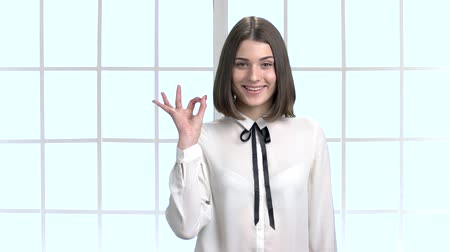 rövidszőrű : Pretty business woman showing ok sign. Happy short hair young woman in white shirt gesturing victory with two fingers, abstract window background.