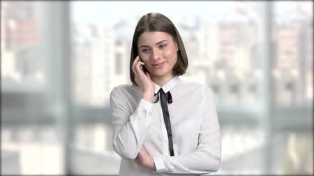 rövidszőrű : Happy young woman talking on cell phone. Beautiful young lady with short hair talking on her smartphone at office.