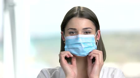 colocando : Close up female doctor puts on a mask. Beautiful young nurse or doctor putting on medical mask on blurred background.