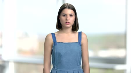 dungarees : Good-looking female student looking astonished. Stylish young girl looking scared on blurred background. Facial expression of fake fear. Stock Footage