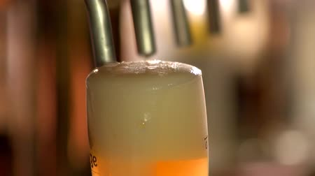 overfill : White beer froth flowing down, slow-mo. Close up beer foam slowly dripping down.