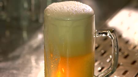 паб : Overfilled dripping glass of beer on the bar table. Glass of draft beer half filled with froth, slow motion.