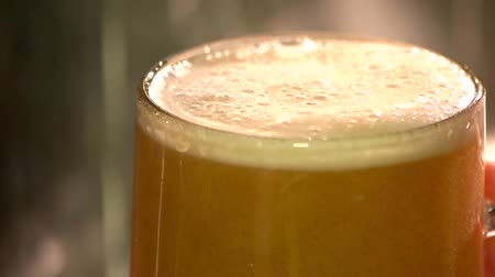 overfill : Extreme close up thick draft ale, slow-motion. Turbid ale glass, macro.