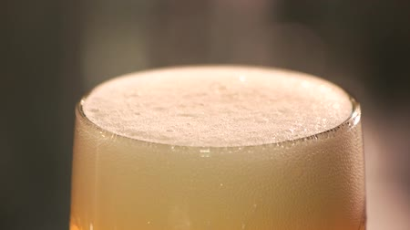 spadek : Close up beer foam reducing slow motion. Macro view creamy beer froth in a glass. Professional beer cut froth.