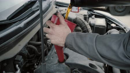 bottleneck : The mechanic changes the oil in the engine of the car Stock Footage
