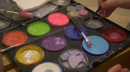 palhaço : Color palette of fine art body painter, close up