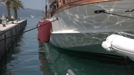 rowboat : Reflections dance on the side of a yacht on the background of waves close-up Stock Footage