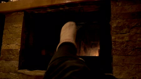 gas burner flame : Girl feet warming in front of fireplace.