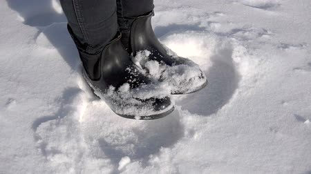 yumuşaklık : The legs of a young girl in snow. The woman froze in a snow-covered winter park.