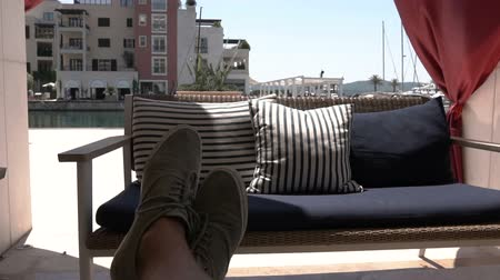 veranda : An empty sofa and a sofa in the summer. Feet of a young man close up. Slow motion