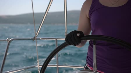 capitão : Closeup steering wheel turning round. Sailing boat with waves splashing