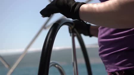 curso : Closeup steering wheel turning round. Sailing boat with waves splashing