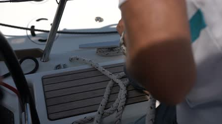 regaty : Sailing man winding sails rope. Filmed from cockpit on beautiful sunny day Wideo