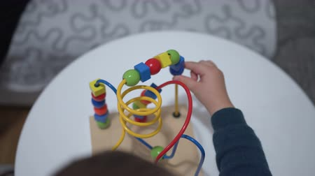 abacus : Child plays with a multi-colored toy. Close up hands