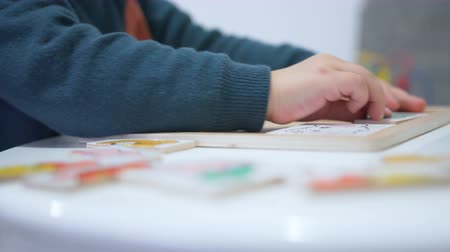 coloured background : Child plays with a puzzle. Close up hands