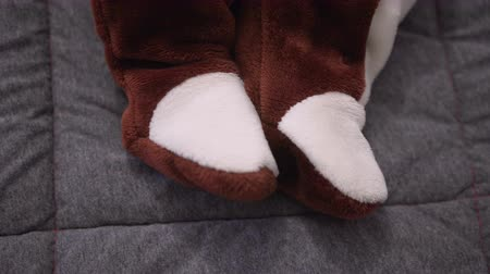 peluş : Baby feet in a plush suit. close up. Cute child playing with rattle on bed.