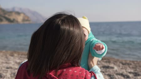 yanak : Baby dressed in a plush suit rabbit turquoise color. Sea and mountains Stok Video