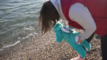peluş : Mom shows her little son the sea for the first time. Baby dressed in a plush suit rabbit turquoise color