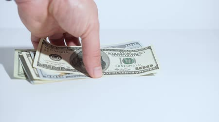 sprzedawca : A mans hand takes the US dollars from the table. White background. Close-up