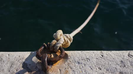 kotva : Mooring bollard and rope attached to a rusty metal mesh