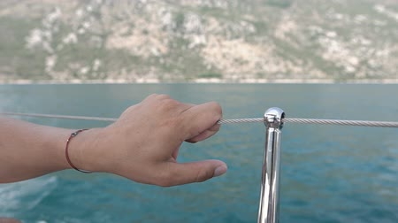 mediterraan : Young Man Holds Onto Railing Of Moving Boat Stockvideo