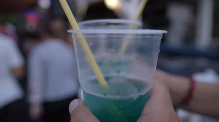 curacao : Hands with cocktails in platick cups hobnobbing, close-up Stock Footage