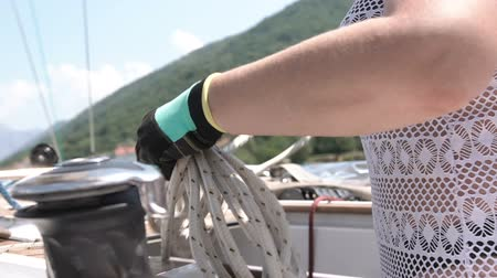 шнур : Woman holds a marine rope, folds it on the deck of the yacht