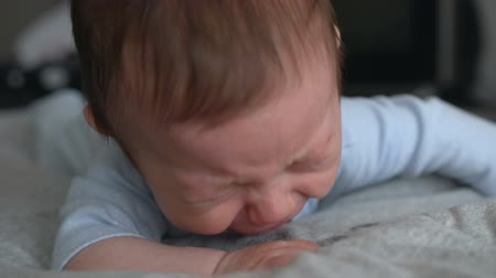 colic : Angry baby lying on front and crying Stock Footage