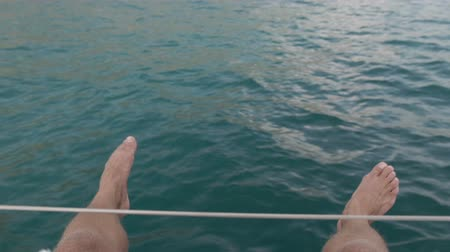 yat yarışı : Young man sits on the deck of a moving yacht and swinging his legs in the air Stok Video
