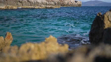 dark bay : Sea swell with coastline rocks. In the foreground are unfocused stones Stock Footage