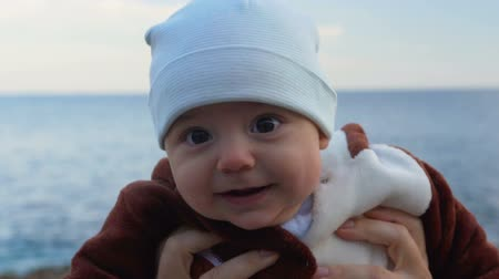 encouraging : Portrait of happy baby boy. Sea and sky in the background. Slow motion