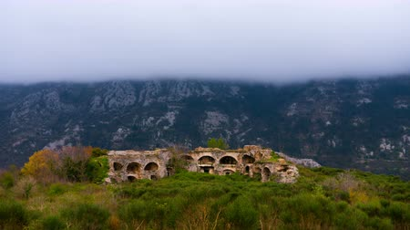 şekillendirme : Time lapse. Clouds forming against the mountain, foreground old fortress